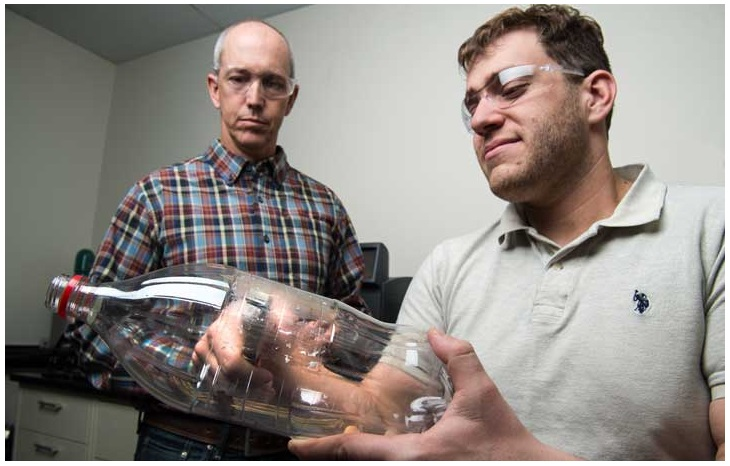 NREL's Bryon Donohoe and Nic Rorrer punch out coupon samples from a PET bottle to test how effectively the PETase enzyme digests plastic. They and Gregg Beckham are among the international team of researchers who are working to further improve the enzyme to allow it to be used industrially to break down plastics in a fraction of the time